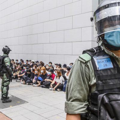 tiotals ghripna demonstranter sitter på marken omgivna av kravallpolis