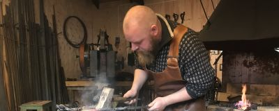 Rolf Eriksson hamrar glödande metall.