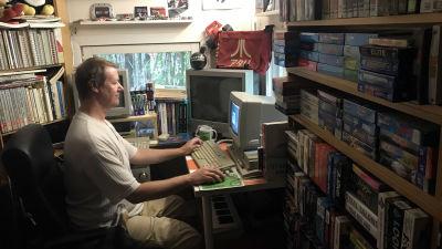 Marko Latvanen varastorakennuksessaan, joka on täynnä tietokoneaiheista tavaraa.