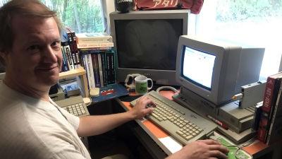 Marko Latvanen työhuoneessaan. Istuu tietokoneella ja katsoo suoraan kameraan hymyillen.