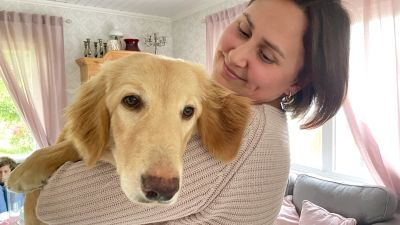 En leende kvinna med brunt hår håller en stor hund i famnen.
