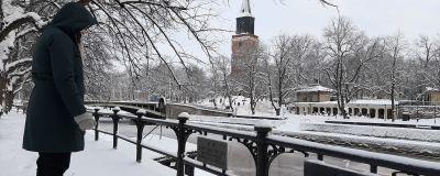 En dam i svarta vinterkläder tittar på två järnskyltar för Aurorasällskapet som hänger på ett staket vid Aura å. I bakgrunden syns Åbo Domkyrka och restaurang Pinella i ett snöigt Åbo.