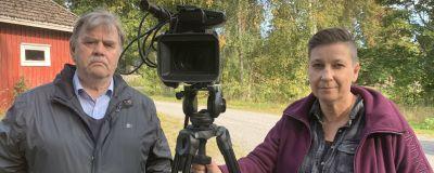 En man och en kvinna står intill en uppriggad videokamera ute på en gårdsplan.