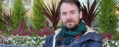 En man i höstjacka och halsduk sitter på en bänk framför en blomrabatt.