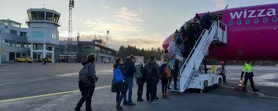 Passagerare stiger på ett av WizzAirs rosa-lilafärgade flygplan på Åbo flygplats.