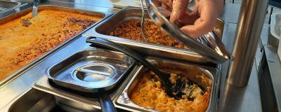 En hand lyfter på locket till ett kärl med en pastasås i en skolmatsal.