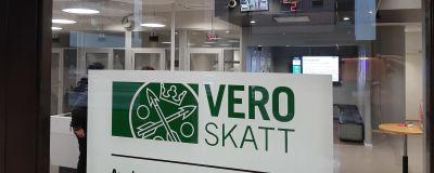 En skylt med texten Vero Skatt, på glasdörren in till ett skattekontor.