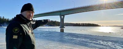 En sjöbevakare står och pekar ut mot isen under Emsalö bro.