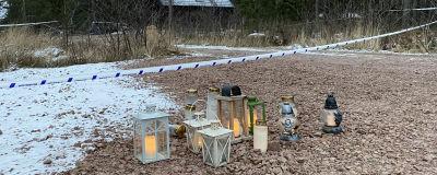 En stuga vars gård är avspärrad med polistejp, lyktor och gravljus på marken.