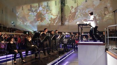 Kapellmäsatren Jukka Untamala i vit skjorta leder Åbo filharmoniska orkester i Åbo konserthus, där en barockmålning med änglamotiv projiceras på väggen.