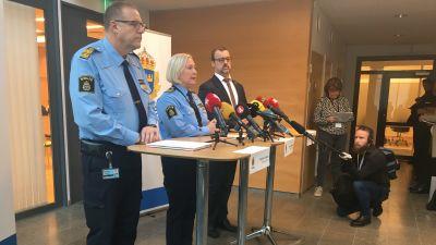 Tre personer står framför mikrofoner.