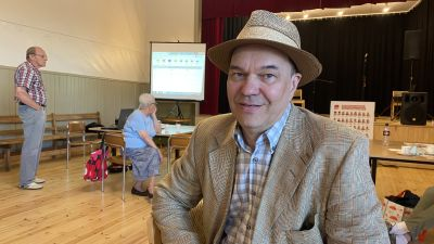 En medelålders man i kavaj och hatt.
