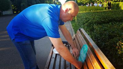 Vasilij Grjaznov limmar klistermärken med uppmaning att hålla avstånd också på parkbänkarna.