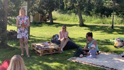 En kvinna i klänning står och pratar framför kvinnor som sitter i gräset på picnic