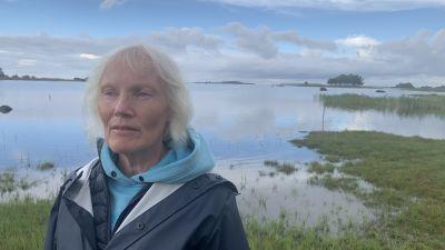 En kvinna i regnrock står vid en havsstrand