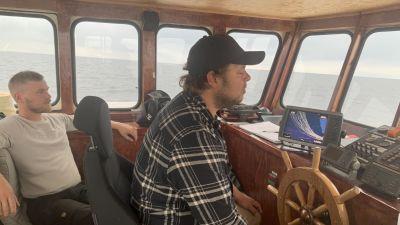 Två män sitter i styrhytten på en fiskbåt