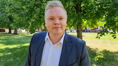 Kulturminister Antti Kurvinen, en blond medelålders man klädd i blå kostym, står under ett träd och tittar in i kameran.