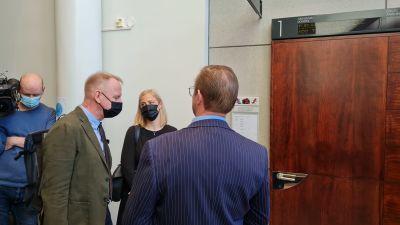 Den åtalade står utanför rättssalen med sina två försvarsadvokater.