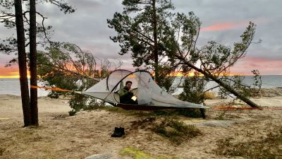 En man ligger i ett trädtält intill havet.
