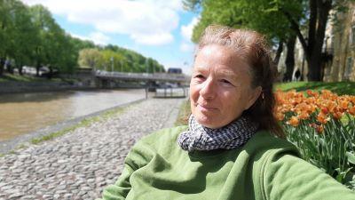 Marjan Raar, en dam med bruntgrått bakåtkammat hår, scarf och en grön tröja, sitter på en bänk vid åstranden med tulpaner bakom sig.