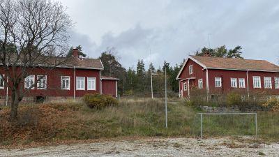 Röda stugor står på en sluttning.