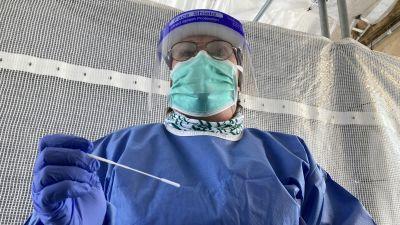 En skötare klädd i skyddsutrustning står framför kameran, redo att utföra ett coronatest.