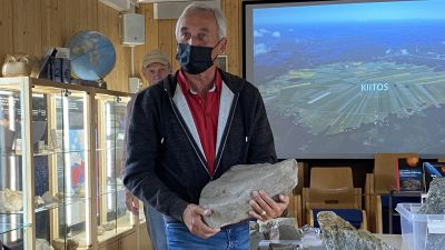 En man med munskydd står och håller i en sten med fossil från miljontals gamla kryp.