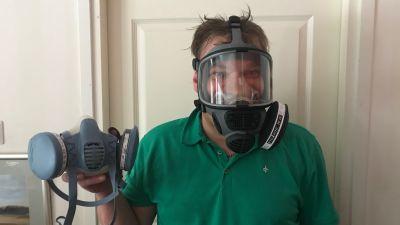 En man grön pikéskjorta bär en gasmask på huvudet. I handen håller han i en annan gasmask.