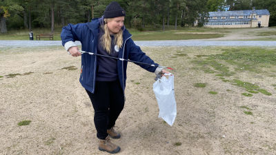 En kvinna står vid en strand och plockar skräp.