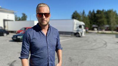 En ljushårig man i solglasögon står på en parkering.
