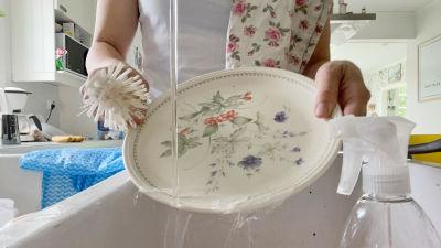 En kvinnas händer syns medan hon diskar ett blommigt fat i diskhon.