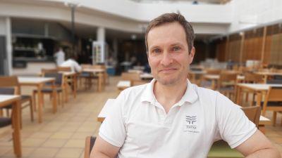 Eljas Honka-Hallila, en man med vit skjorta och mörkt hår, sitter i en stor matsal.