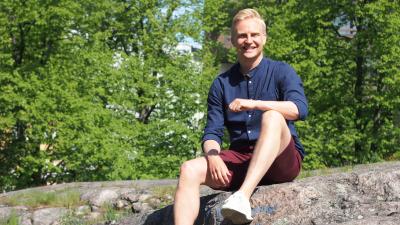 En man i skjorta på en sten i skogen en solig dag.