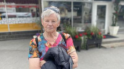 Solveig Ljungberg, en kvinna med kort, grått hår iklädd en tunika i rosa, turkost och orange.