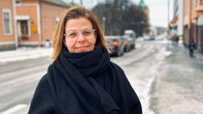 Kvinna i svart jacka och halsdukstår på en trottoar.