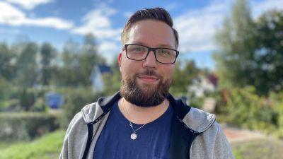 Porträttfotografi av ung man med kort brunt hår, glasögon och skägg. Mannen står utomhus med grönskande bakgrund. Han har på sig en grå collagejacka och blå t-skjorta. Runt halsen bär han ett diabeteshalsband.