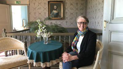 Kaija Hartiala sitter i den gustavianska salen på Brinkhall.