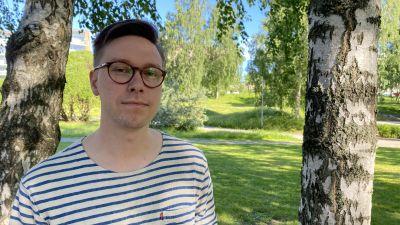 En ung man iklädd glasögon och randig tröja står i en lummig miljö, med gräsmattor och träd i bakgrunden.