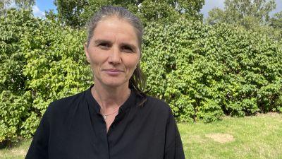 Jenny Madestam står på en gräsmatta och tittar in i kameran.