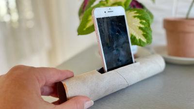 En tom hushållspappersrull ligger på bordet. Ett hål har klippts i rullen och där har en mobiltelefon placerats.