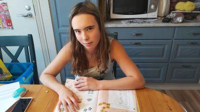 Flicka vid bord med skolbok.