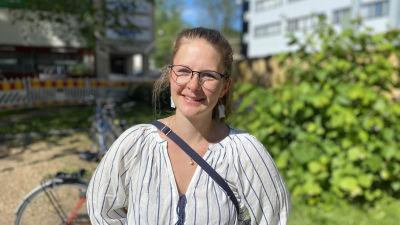 Jutta Maunula, en kvinna med mellanblont uppsatt hår och glasögon, ler mot kameran.