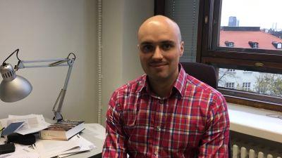 Bild på forskare Ryhor Niznikau på hans kontor på utrikespolitiska institutet.