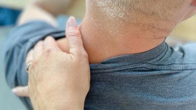 En man sitter när en annans hand vilar på hans axel. Han har ryggen vänd mot kameran.