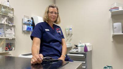 En kvinnlig veterinär sitter i sitt mottagningsrum på veterinärkliniken.