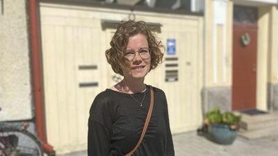 Nea Kronberg, en kvinna med kort och lockigt hår och runda glasögon.
