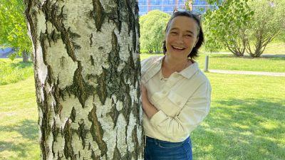 Nina Hukkinen kikar fram bakom ett träd.