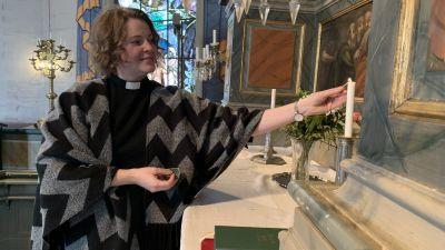 Kvinna tänder ljus i kyrka.