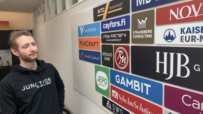 Frank Sandqvist framför en vägg med företagslogotyper.