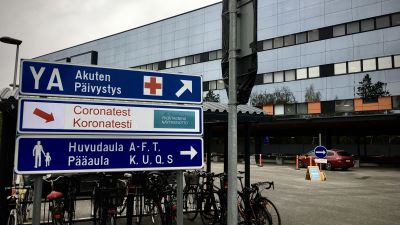 Skylt vid Vasa centralsjukhus där det står bland annat Coronatest. I bakgrunden syns teststället.